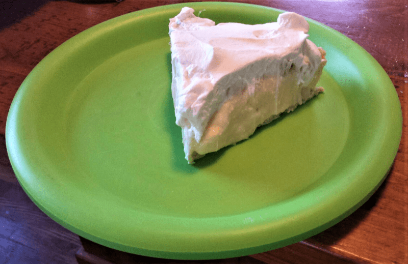 A slice of banana cream pie on a green plate